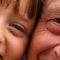 Close up detail of a young girl and her grandfather with their faces pressed close together.