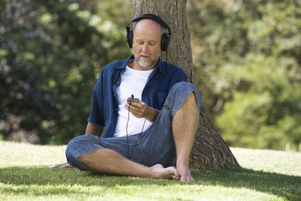 A senior man listening to music
