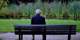 vecchio-uomo-di-spalle-su-una-panchina-al-parco-min