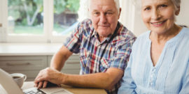 Portrait of smiling senior couple using laptop